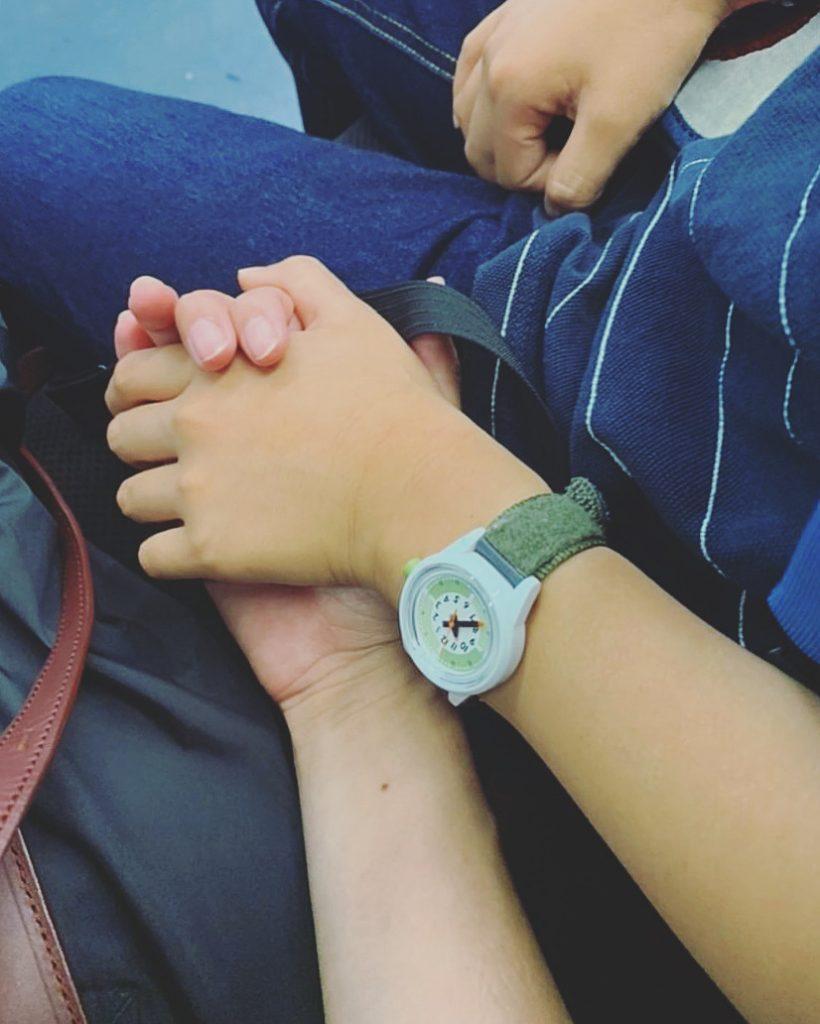 小学生の男の子がママと手をつないでいる写真